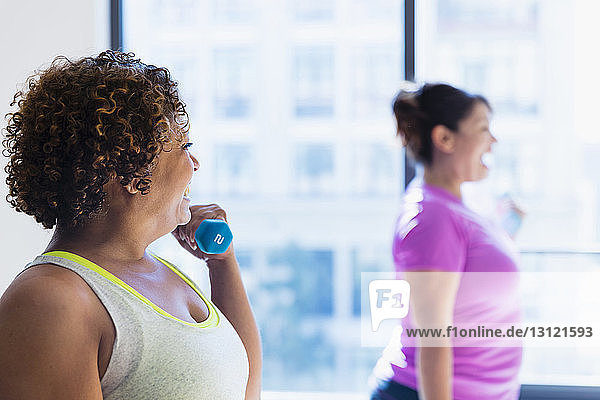 Happy friends lifting dumbbells while exercising against window in yoga studio