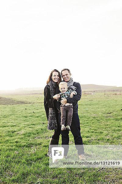 Porträt von glücklichen Eltern  die ihren Sohn tragen  während sie auf einem Grasfeld vor klarem Himmel stehen
