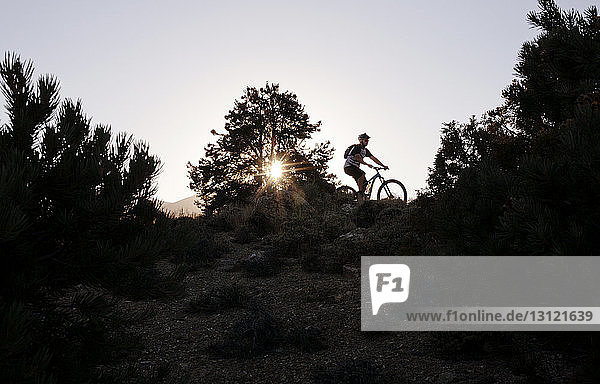 Mann fährt bei Sonnenuntergang auf dem Berg