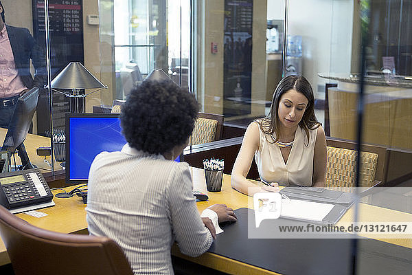 Businesswomen discussing about document at desk in office