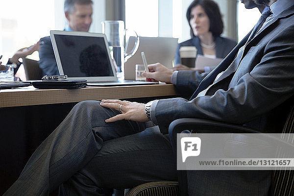 Geschäftsmann sitzt während einer Besprechung im Büro am Schreibtisch