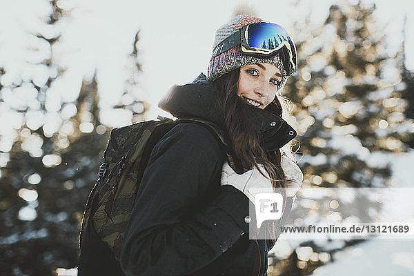 Porträt einer selbstbewussten jungen Frau mit Rucksack  die im Winter eine Skibrille trägt