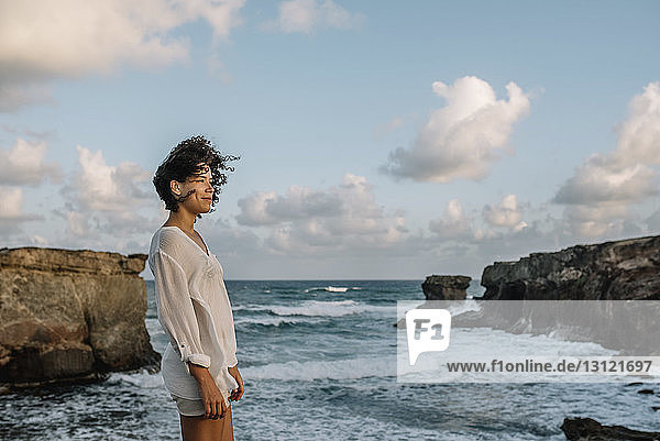 Woman looking at view while standing at beach against cloudy sky