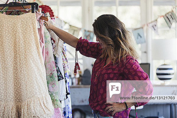 Side view of woman with hand on hip looking at costumes while standing in office