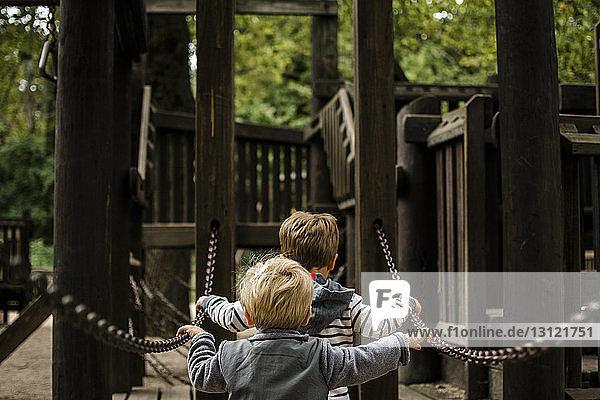 Rückansicht der Brüder  die auf dem Spielplatz eine Kette gegen die Dschungelturnhalle halten