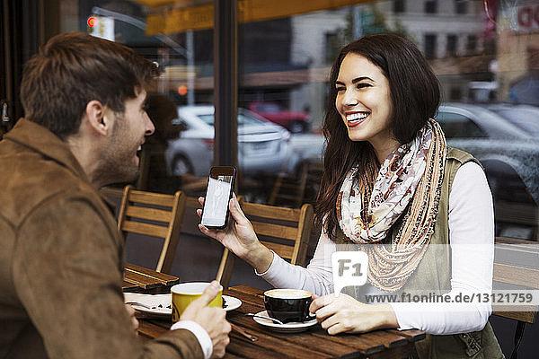 Glückliche Frau zeigt ihrem Freund ihr Handy  während sie im Café Kaffee trinkt