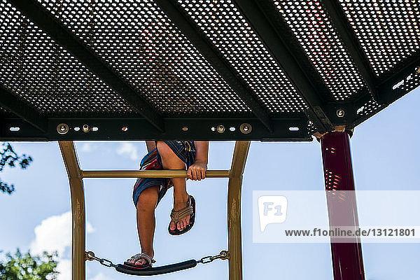 Niedriger Abschnitt eines Jungen  der auf eine Leiter auf einem Spielplatz klettert
