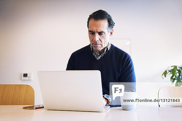 Serious man looking at laptop computer while sitting at table against wall