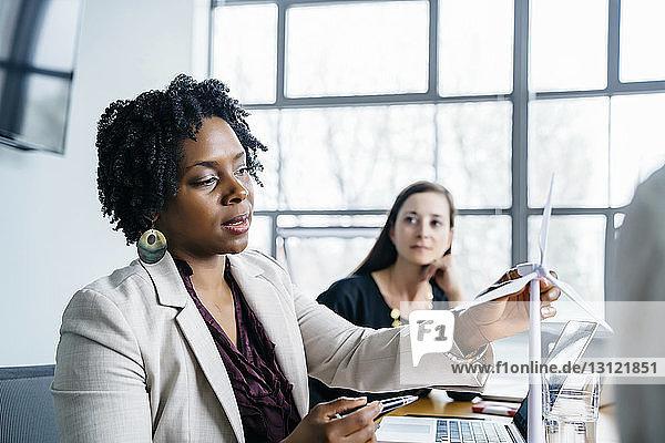Geschäftsfrau erklärt Kollegen im Büro das Modell einer Windkraftanlage
