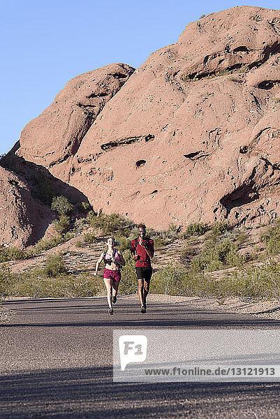 Wanderer  die bei Sonnenschein auf der Strasse gegen Felsformationen laufen