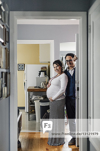 Porträt eines zu Hause stehenden werdenden Ehepaares