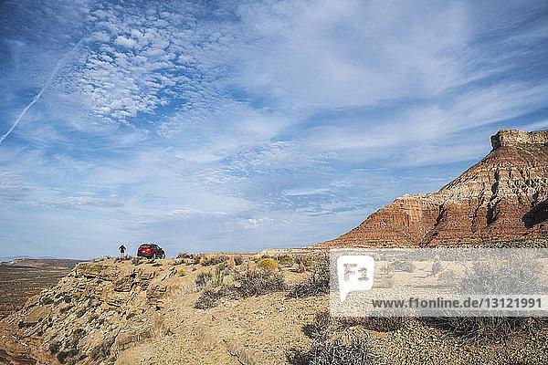 Fernansicht einer Frau  die auf dem Gipfel eines Berges im Auto gegen den Himmel steht