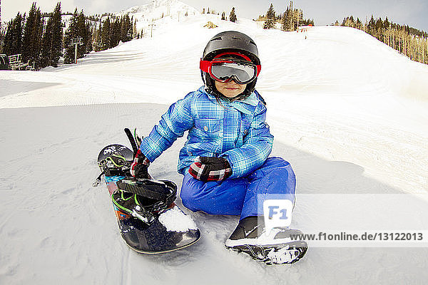 Girl wearing ski goggles sitting by snowboard on snow covered field