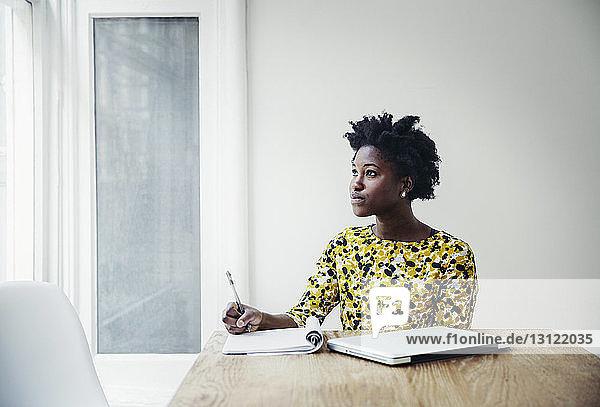 Nachdenkliche Geschäftsfrau schreibt in Buch am Schreibtisch im Sitzungssaal