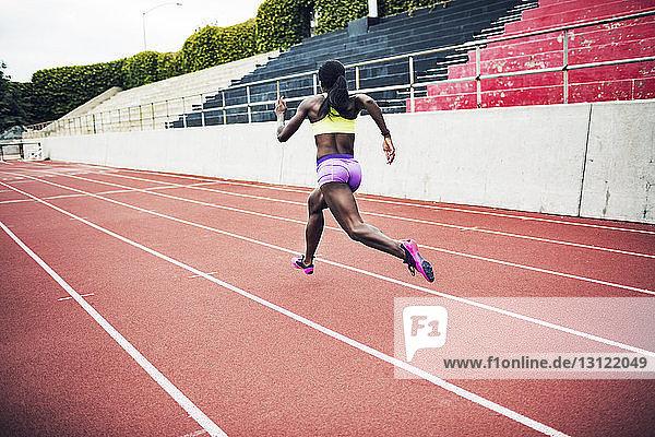 Rückansicht eines entschlossenen Athleten  der auf Bahnen läuft