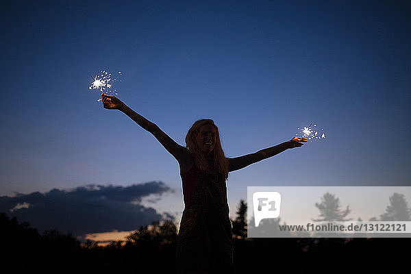 Cheerful woman with arms outstretched holding sparklers against sky at night