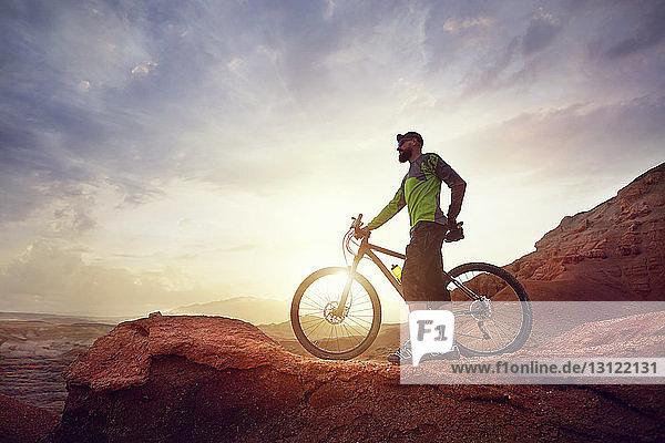 Full length of hiker with mountain bike standing on rocks against sky at desert during sunset