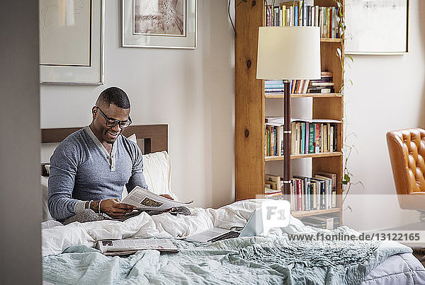 man reading newspaper while sitting on bed at home