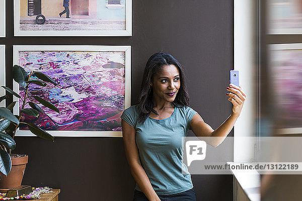 Frau nimmt Selbstliebe  während sie sich zu Hause an Bilderrahmen an der Wand stellt