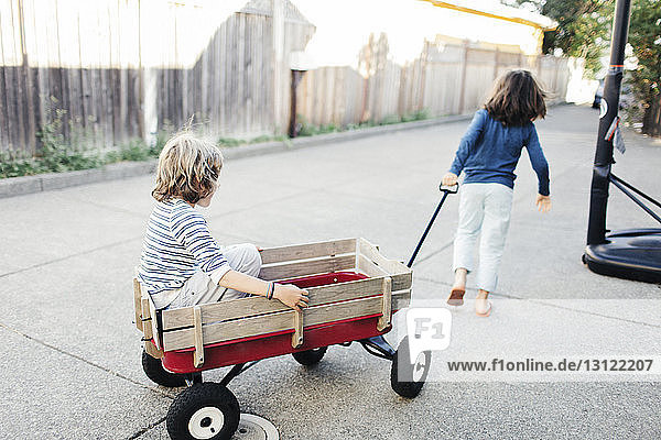 Rear view of boy pulling brother in toy wagon at yard