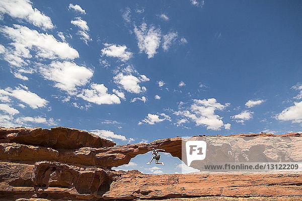 Frau springt auf Felsformation gegen den Himmel