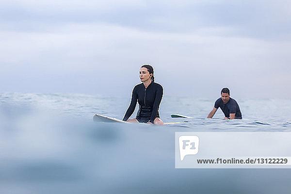 Freunde sitzen auf einem Surfbrett im Meer gegen den Himmel