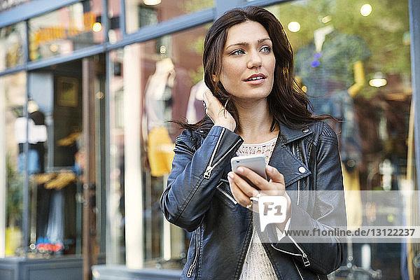 Nachdenkliche Frau hält Smartphone vor dem Geschäft