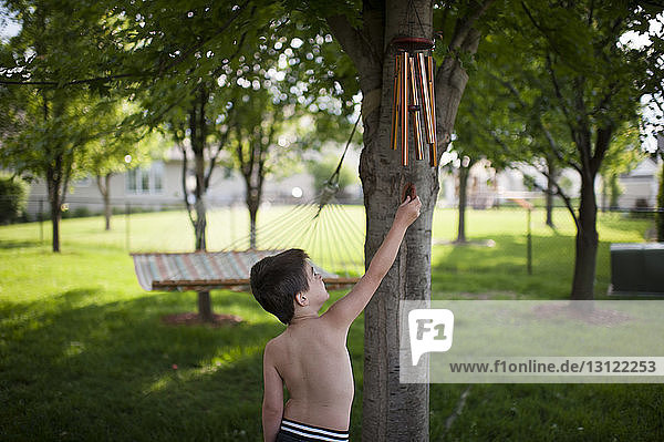 Shirtless boy playing with wind chime while standing at backyard