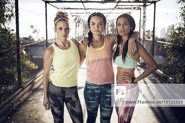 Porträt von selbstbewussten Sportlern auf der Brücke stehend
