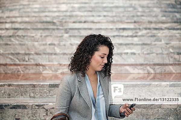 Geschäftsfrau benutzt Smartphone auf Treppen im Freien
