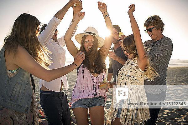 Fröhliche Freunde tanzen am Strand
