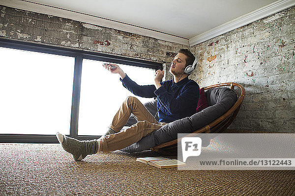 Man enjoying music while sitting on chair by window at home