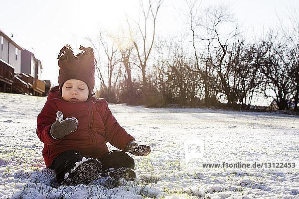 Junge in warmer Kleidung sitzt auf schneebedecktem Feld im Hinterhof