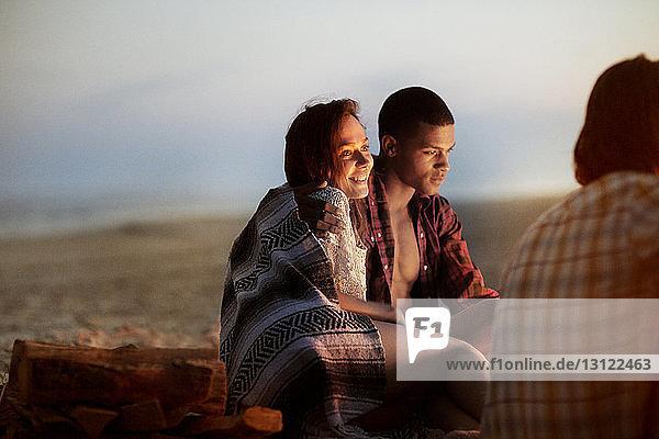 Glückliche Frau sitzt mit Mann in der Abenddämmerung am Strand Glückliche Frau sitzt mit Mann in der Abenddämmerung am Strand