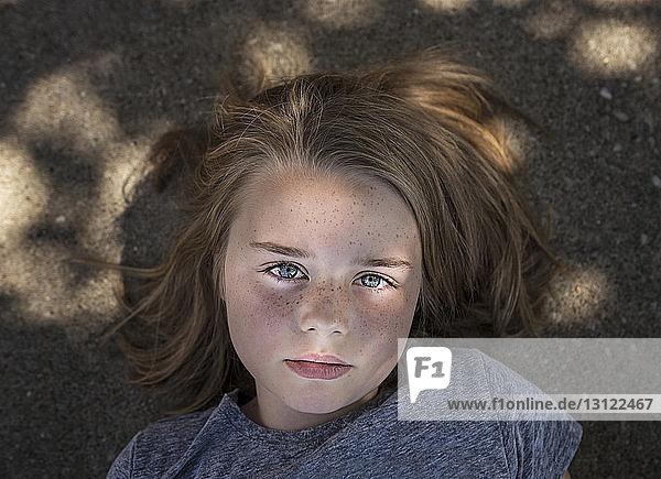Overhead portrait of confident girl lying on road