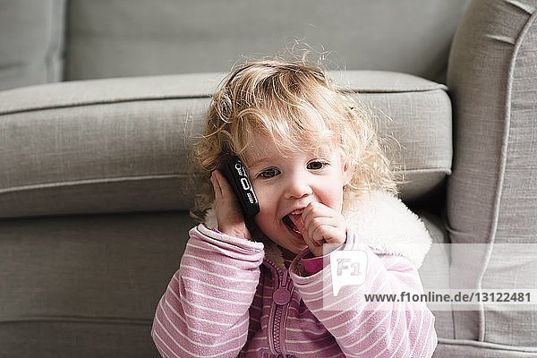 Girl talking on mobile phone by armchair at home