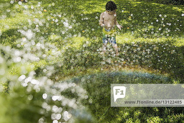 High angle view of water sprinkling over boy playing in backyard