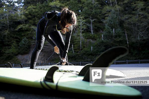 Frau im Neoprenanzug bereitet Surfbrett am Strand vor Frau im Neoprenanzug bereitet Surfbrett am Strand vor