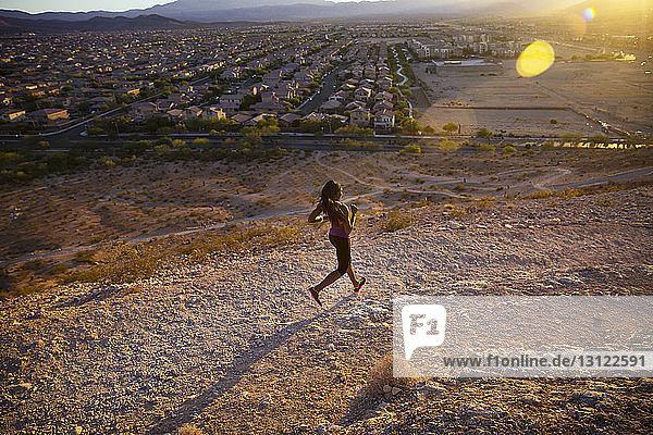 Hochwinkelaufnahme eines Joggers auf einem Hügel bei einem Dorf während eines sonnigen Tages
