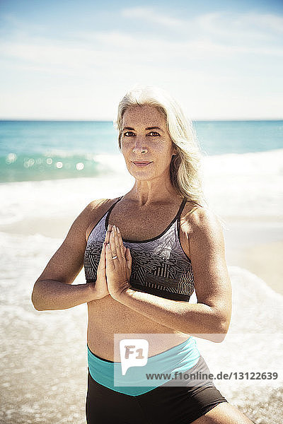 Portrait of confident woman practicing yoga in tree pose at Delray beach