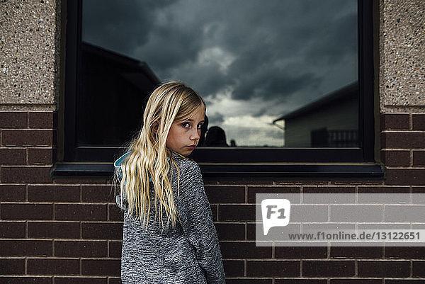 Porträt eines Mädchens  das vor dem Haus steht