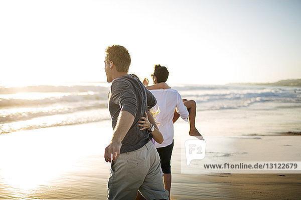 Rückansicht von Paaren  die am Strand gegen den klaren Himmel laufen
