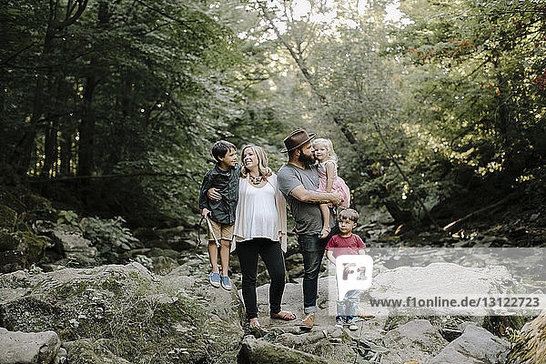 Glückliche Eltern mit Kindern  die sich im Wald vergnügen