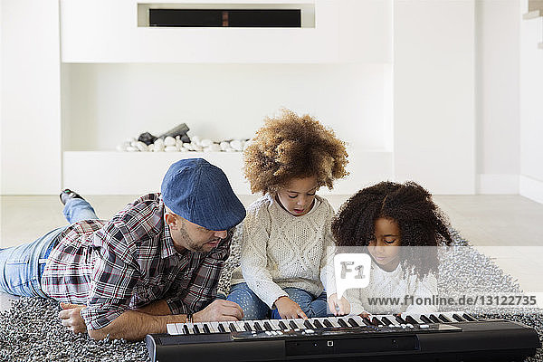 Father and daughters playing keyboard instrument on carpet at home