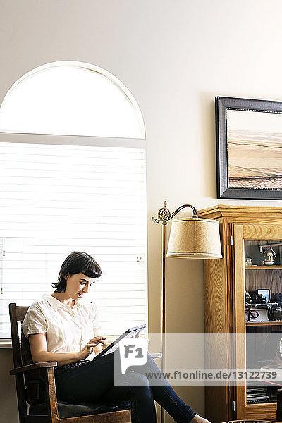 Seriöse Frau benutzt digitales Tablett  während sie zu Hause am Bogenfenster sitzt