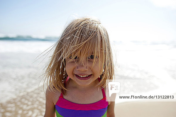 Close-up portrait of smiling girl standing on shore at beach