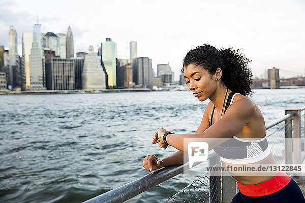 Female athlete checking smart watch while standing by river against sky in city