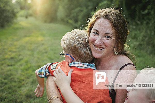 Porträt einer Mutter mit Söhnen auf einem Grasfeld im Wald sitzend