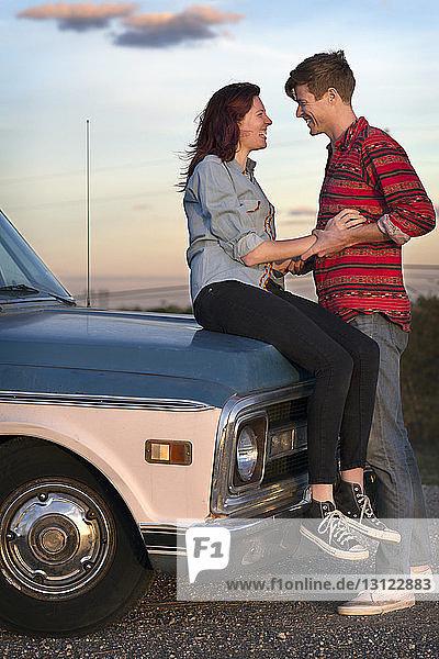 Mann schaut Frau an  die auf einem Pick-up sitzt
