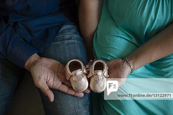 Mittelteil eines werdenden Paares  das zu Hause sitzt und Babyschuhe hält